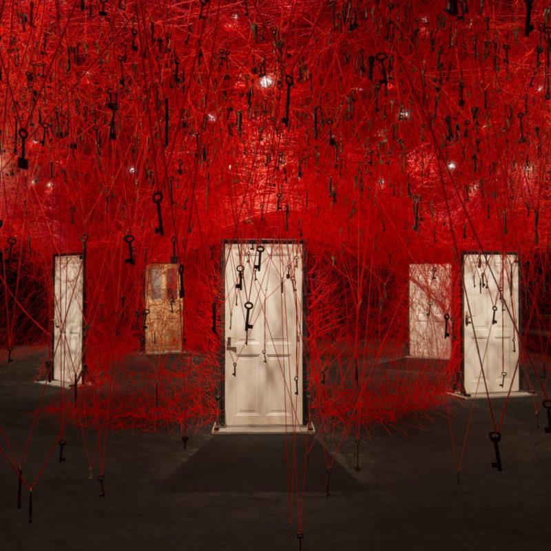 """The Locked Room"", 2016, Installation: old keys, old wooden doors, red wool, KAAT Kanagawa Arts Theatre, Yokohama, Japan, Photo by Masanobu Nishino, © SIAE, Rome, 2020 and the artist"