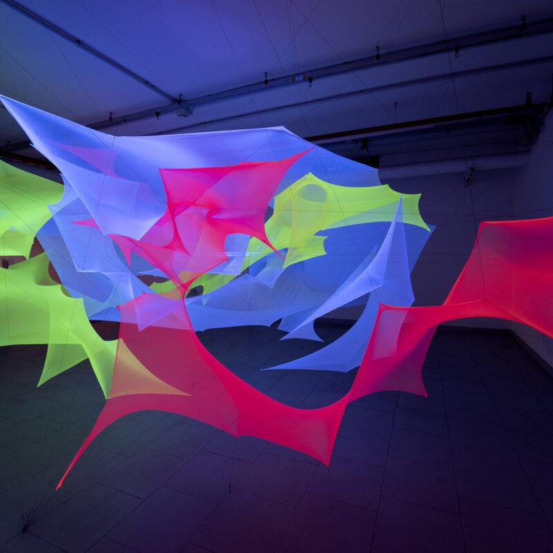 """C Installation"", 2020, 2x5x5 m, spandex, thread and violet light, copyright Nei Albertì"